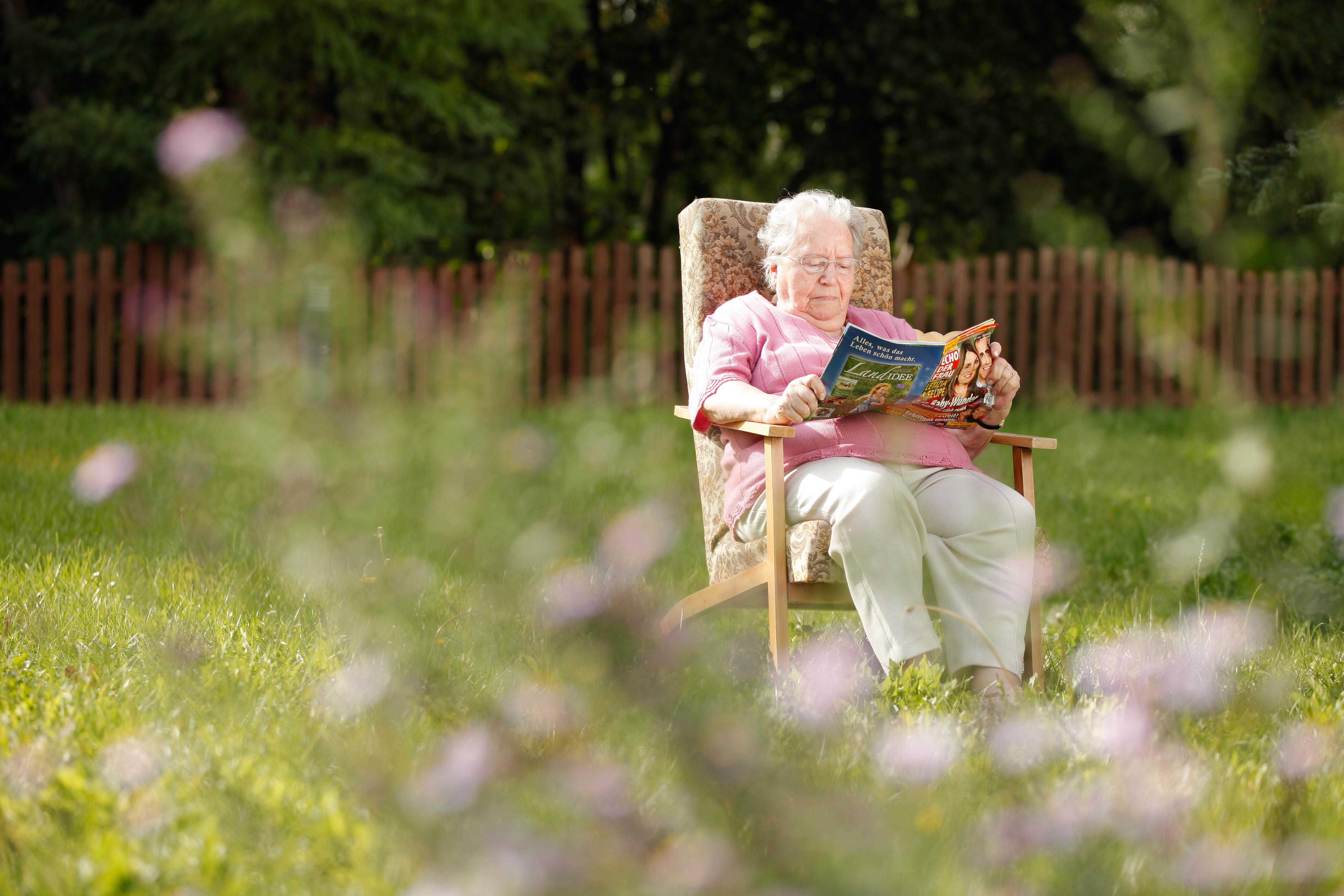 Eine Seniorin sitzt im Garten